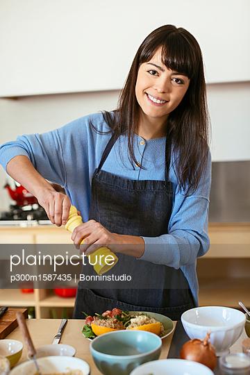 Portrait of smiling woman in kitchen - p300m1587435 von Bonninstudio