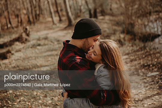 Happy mid adult couple embracing in forest - p300m2274840 by Gala Martínez López