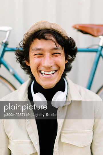 Cheerful man squinting eyes in front of bicycle - p300m2287149 by Lightsy Studio