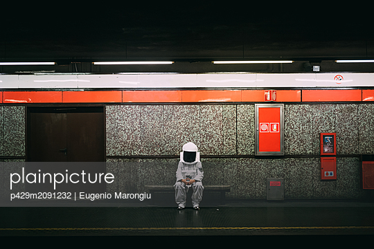 Astronaut waiting on train platform - p429m2091232 by Eugenio Marongiu