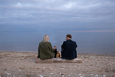 Young couple with tea resting on lake shore - p1166m2235279 by Cavan Images