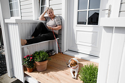 Relaxed senior woman sitting on porch with her dog - p300m2103194 by Katharina Mikhrin
