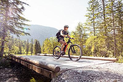 Woman riding  e-mountain bike in the mountains - p300m2131847 by Florian Küttler