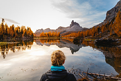 Female hiker looking at the mountain landscape with lake at the first light of the day, Dolomites Alps, Cortina, Italy - p300m2144515 by Michela Ravasio