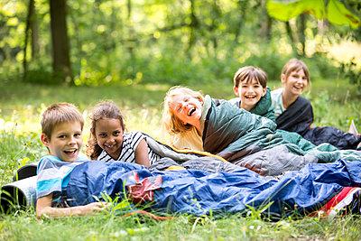 School children camping in forest, lying in sleeping bags - p300m2160746 by Fotoagentur WESTEND61