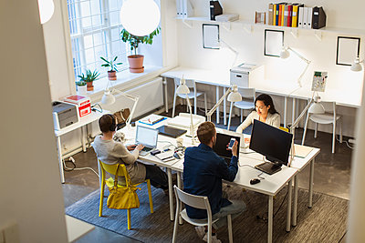 High angle view of multi-ethnic colleagues using technologies at desk in creative office - p426m1588264 by Kentaroo Tryman