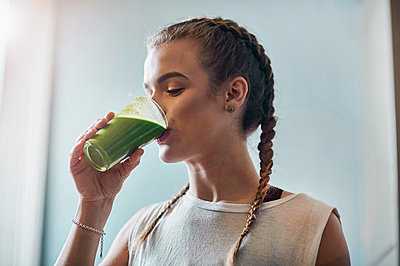 Young woman drinking vegetable smoothie in kitchen - p429m1469566 by Matt Lincoln