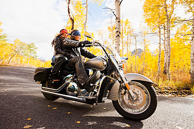 Caucasian couple riding motorcycle - p555m1464324 by Mike Kemp