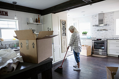 Senior woman downsizing, packing and sweeping kitchen - p1192m2010071 by Hero Images