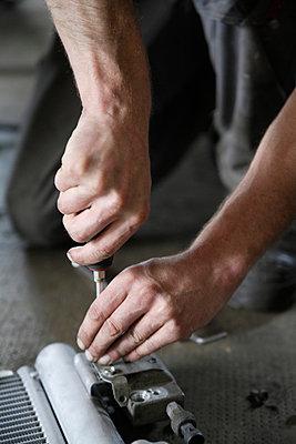 Germany, Ebenhausen, Mechatronic technician working in car garage - p30020015f by Tom Chance