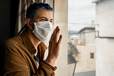 Man wearing protective mask and looking out of the window - p300m2189481 by Rafa Cortés