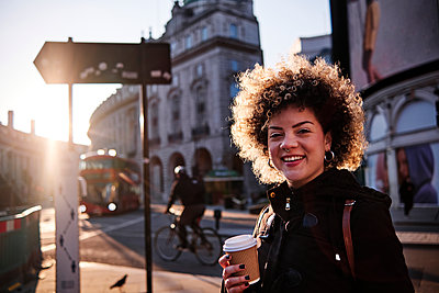 Smiling hipster woman having coffee during sunny day in city - p300m2273651 by Angel Santana Garcia