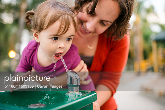 Mother helping daughter in drinking water from fountain - p1166m1509159 by Cavan Images