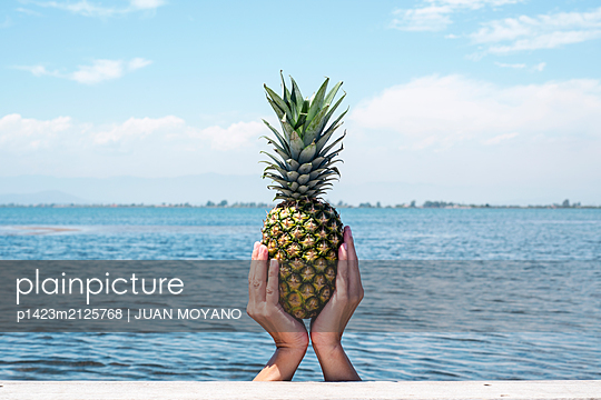 Man with a pineapple in his hands in a pier - p1423m2125768 by JUAN MOYANO