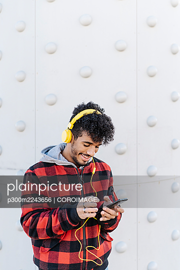 Young man smiling while using mobile phone standing against wall - p300m2243656 by COROIMAGE
