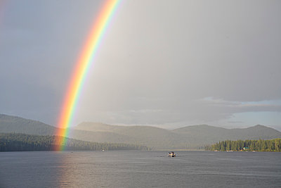 Vivid rainbow over calm lake with boat near shore in countryside - p1166m2212353 by Cavan Images