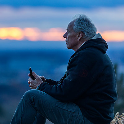 Seated man holding smart phone at sunset - p1427m2109960 by Steve Smith
