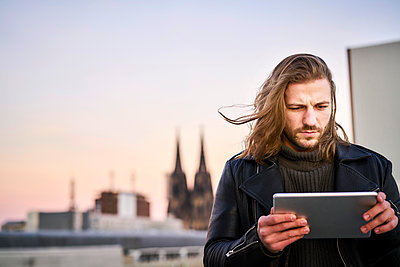 Germany, Cologne, portrait of bearded young man using digital tablet - p300m2079601 by Jo Kirchherr