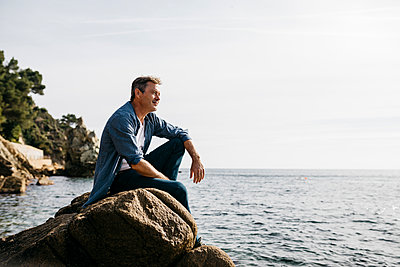 Thoughtful mature man sitting on rock against clear sky - p300m2252956 by Josep Rovirosa