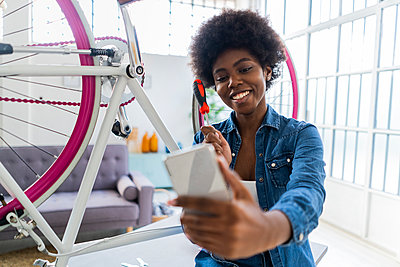 Smiling young woman with screwdriver taking selfie through mobile phone at home - p300m2274820 by Giorgio Fochesato