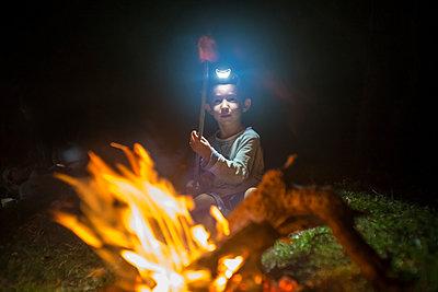 Boy roasting marshmallows in campfire - p343m1578158 by Konstantin Trubavin