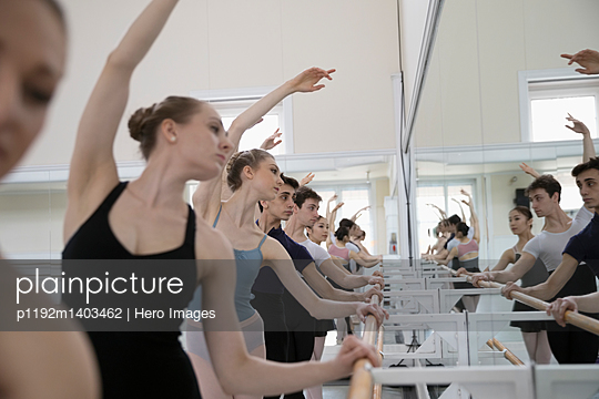 Ballet dancers practicing in a row at barre in dance studio