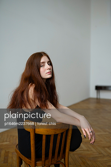 Young woman with brown hair sits on a chair - p1646m2237668 by Slava Chistyakov
