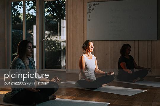 Women meditating in yoga studio - p312m2208270 by Plattform