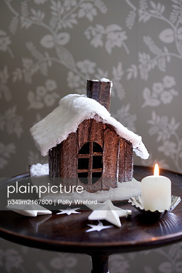 Model cabin and lit candle on antique wooden side table. - p349m2167800 by Polly Wreford