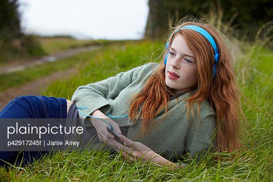 Teenage girl listening to headphones - p42917245f by Janie Airey