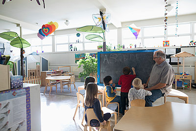 Senior volunteer and preschool students at blackboard in classroom - p1192m1560212 by Hero Images