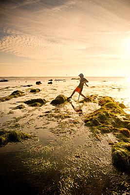 Teenage boy exploring tide pools in La Jolla, California - p1427m2109944 by Stephen Simpson