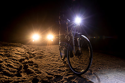 Cyclist followed by car at night in winter - p1687m2278816 by Katja Kircher