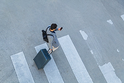 Businessman with baggage crossing the street while looking at cell phone, top view - p300m1205124 by Tom Chance