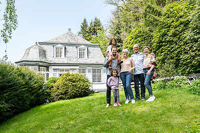 Happy extended family standing in garden of their home - p300m2132276 by MiJo