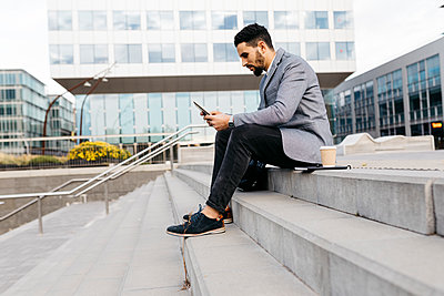 Casual young businessman sitting on stairs in the city using tablet - p300m2160169 by Josep Rovirosa