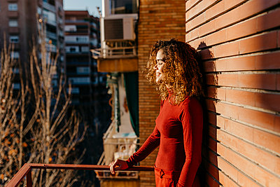 Portrait of Brazilian woman on an urban balcony with sunset light on her face in Granada, Spain - p300m2171311 von Tania Cervián