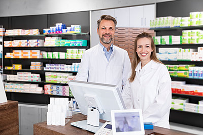 Smiling male and female pharmacist standing at checkout in store - p300m2251238 by Florian Küttler