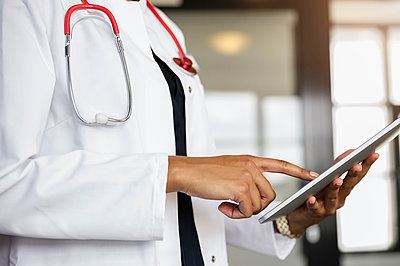 Female healthcare worker using digital tablet at hospital corridor - p300m2281532 by Buero Monaco