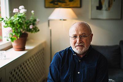 Portrait of confident senior man sitting at home - p426m1130989f by Maskot