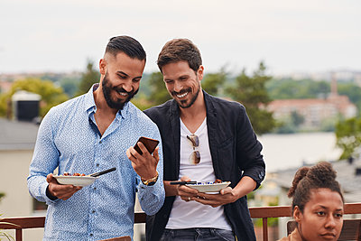 Smiling man showing mobile phone to friend while holding meal during party on terrace - p426m2074473 by Maskot
