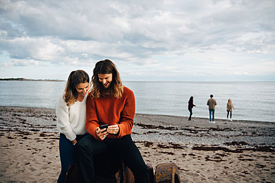 Couple looking at mobile phone while sitting on sea shore at beach - p426m2149225 by Maskot