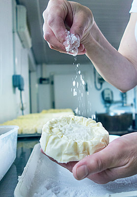 Female cheesemaker sprinkling cheese, close up of hands - p429m2019510 by Seb Oliver