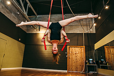 Caucasian acrobat hanging from ropes in studio - p555m1412622 by Inti St Clair photography
