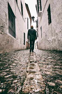 Rearview man walking up old street in Ronda, Spain  - p597m2063504 by Tim Robinson