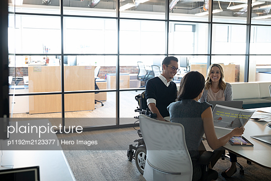 Businessman in wheelchair listening to colleagues in meeting - p1192m2123377 by Hero Images