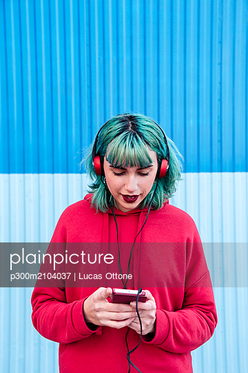 Portrait of young woman with blue dyed hair listening music with headphones looking at smartphone - p300m2104037 by Lucas Ottone