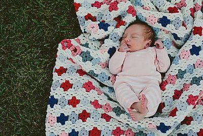 Overhead view of baby girl sleeping on blanket in yard - p1166m1183126 by Cavan Images