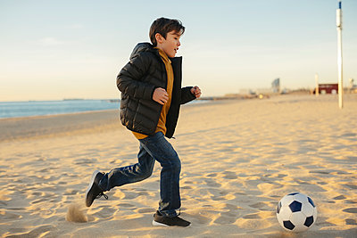 Father and son playing football on the beach - p300m1562600 by Bonninstudio