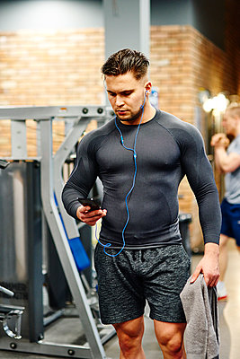 Man using cell phone at the gym - p300m1581612 by gpointstudio